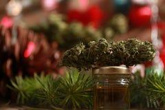 Lubrifichi la cannabis in una bottiglia e la canapa su un fondo di natale immagini stock