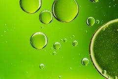 Lubrifique as gotas na água, bolhas no fundo abstrato verde Fotografia de Stock Royalty Free