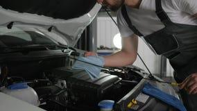 Lubrifique o medidor de óleo nas mãos auto reparador, mecânicos que verificam o nível de óleo, sistemas de diagnósticos máquina,  video estoque