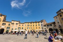 Piazza Anfiteatro - Lucca Tuscany Italy. LUCCA, ITALY - APRIL 16, 2017: Tourists and locals visit the ancient Town square Piazza dell`Anfiteatro - Amphitheater Stock Photos