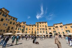 Piazza Anfiteatro - Lucca Tuscany Italy. LUCCA, ITALY - APRIL 16, 2017: Tourists and locals visit the ancient Town square Piazza dell`Anfiteatro - Amphitheater Stock Photography