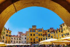 Piazza del Anfiteatro in Lucca, Tuscany, Italy. Lucca, Italy, - July 01, 2016: Piazza del Anfiteatro with unidentified people. The ring of buildings surrounding Stock Images