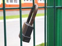 Lucchetto arrugginito bloccato sul recinto Immagine Stock