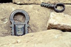 Lucchetto d'annata russo con la chiave su un fondo delle pietre Fotografie Stock Libere da Diritti