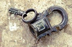 Lucchetto d'annata russo con la chiave su un fondo delle pietre Fotografia Stock Libera da Diritti