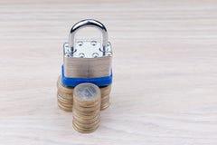Lucchetto su una pila di monete Fotografie Stock