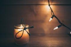 Luce arancio del fondo di legno con la candela immagine stock