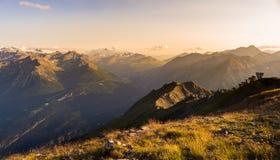 Luce calda al tramonto sui picchi, sulle creste e sulle valli di montagna Immagini Stock