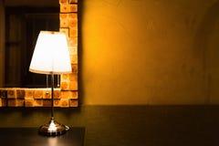 Luce calda brillante della lampada da tavolo sulla parete di lerciume Fotografie Stock Libere da Diritti