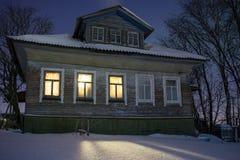 Luce calda casa russa ofcozy del villaggio delle finestre dalla vecchia nel freddo amaro Paesaggio di notte di inverno con neve e Immagini Stock