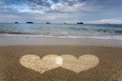 Luce dei cuori in sabbia sulla spiaggia dell'oceano Fotografia Stock