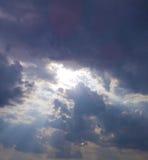 Luce dei Raggi di indicatore luminoso attraverso le nubi scure il sole splende dalla c Immagine Stock Libera da Diritti