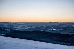 Luce del giorno dalla collina di Ochodzita in montagne di Beskid Slaski di inverno sopra il villaggio di Koniakow in Polonia con  fotografia stock libera da diritti
