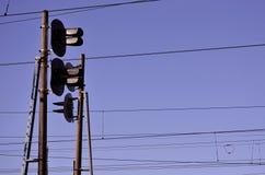 Luce del traffico ferroviario contro chiaro cielo blu, filo di contatto Linee elettriche ad alta tensione della ferrovia su spiri Fotografia Stock