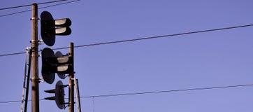 Luce del traffico ferroviario contro chiaro cielo blu, filo di contatto Linee elettriche ad alta tensione della ferrovia su spiri Immagine Stock Libera da Diritti