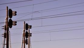 Luce del traffico ferroviario contro chiaro cielo blu, filo di contatto Linee elettriche ad alta tensione della ferrovia su spiri Immagini Stock Libere da Diritti