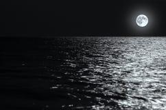Luce della luna sulle onde alla notte nel mare sulle esposizioni lunghe immagini stock