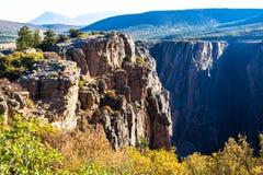 Luce di alba sulle scogliere ripide e sul fogliame indigeno del canyon nero del parco nazionale di Gunnison in Colorado immagine stock