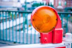 Luce di barriera d'avvertimento della via della costruzione arancio sulla barriera Costruzione di strade sulle vie delle città eu fotografie stock libere da diritti