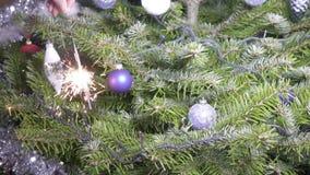 Luce di Bengala contro lo sfondo di un albero di Natale con le palle del ` s del nuovo anno, rallentatore video d archivio