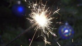 Luce di Bengala contro lo sfondo di un albero di Natale con le palle del ` s del nuovo anno, rallentatore archivi video