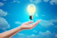 Luce di lampadina di idee su una mano Fotografia Stock