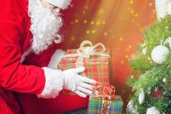 Luce di Natale ed ispirazione con Santa Claus che mette il contenitore di regalo Immagini Stock Libere da Diritti