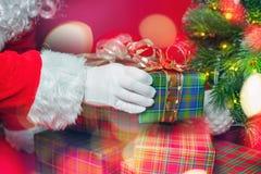 Luce di Natale ed ispirazione con Santa Claus che mette il contenitore di regalo Fotografia Stock
