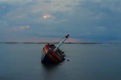 Luce di sera con un naufragio in mare Immagine Stock Libera da Diritti