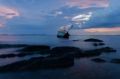 Luce di sera con un naufragio in mare Immagini Stock
