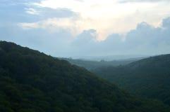 Luce di sera sopra la valle boscosa Fotografia Stock