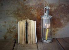 Luce di una lampada dell'annata e del vecchio libro sulla tavola di legno Immagini Stock