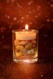 Luce dorata delle candele che bruciano in vetro della tazza con effetto della luce a Immagini Stock Libere da Diritti