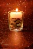 Luce dorata delle candele che bruciano in vetro della tazza con effetto della luce a Fotografia Stock Libera da Diritti
