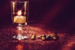 Luce dorata delle candele che bruciano in vetro di vino con effetto della luce Fotografia Stock Libera da Diritti