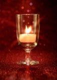 Luce dorata delle candele che bruciano in vetro di vino con effetto della luce Fotografie Stock