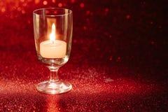 Luce dorata delle candele che bruciano in vetro di vino con effetto della luce Fotografie Stock Libere da Diritti