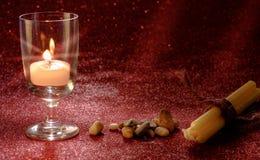 Luce dorata delle candele che bruciano in vetro di vino con effetto della luce Fotografia Stock