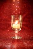 Luce dorata delle candele che bruciano in vetro di vino con effetto della luce Immagini Stock