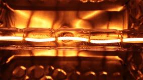 Luce intermittente di una spirale gialla del tungsteno di una lampada alogena stock footage