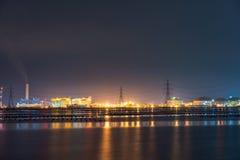 Luce notturna alla fabbrica vicino all'oceano, fabbrica della raffineria di petrolio, centrale petrolchimica, petrolio immagini stock