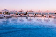 Luce pastello di tramonto sopra i letti di Sun e della piscina fotografie stock libere da diritti