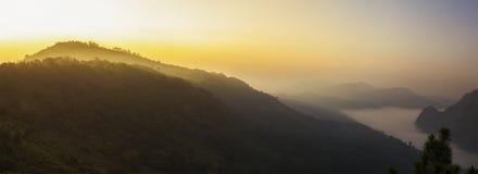 Luce solare arancio sopra l'alta montagna e la nebbia Fotografia Stock Libera da Diritti