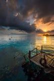 Luce solare che passa la nuvola con un molo di legno nella priorità alta Fotografia Stock Libera da Diritti