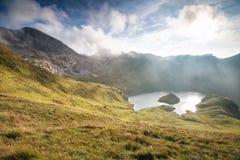 Luce solare luminosa sopra il lago alpino nella caduta Fotografie Stock