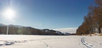 Luce solare sopra il panorama congelato del fiume Fotografie Stock