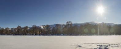 Luce solare sopra il panorama congelato del fiume Immagine Stock