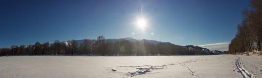 Luce solare sopra il panorama congelato del fiume Fotografia Stock