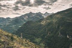 Luce solare sulla valle alpina con i picchi di montagna d'ardore e le nuvole sceniche Le alpi francesi italiane, destinazione di  Immagini Stock Libere da Diritti