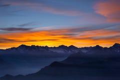 Luce solare variopinta dietro i picchi di montagna maestosi dell'italiano - alpi francesi, osservati da distante Nebbia e foschia Fotografia Stock Libera da Diritti